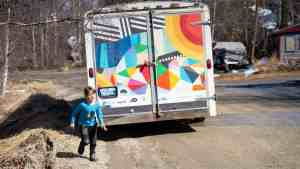 Nora Swan runs to pet a dog to pass the time as families take turns visiting the mobile art gallery in Peace River Flats that her family set up.