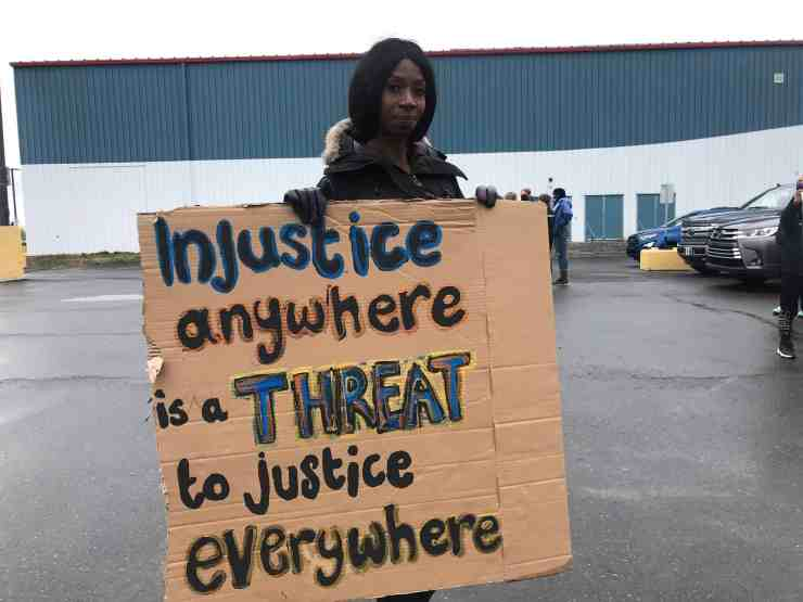 Yellowknife resident Inemesit Graham awaits the start of Tuesday's protest