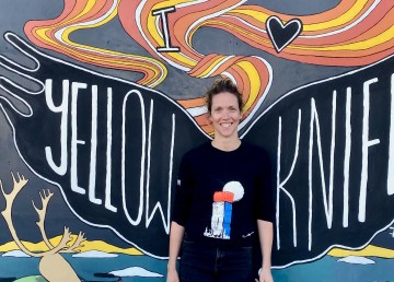 Heather Duinker in front of the finished I Love YK mural outside Weaver and Devore. Photo: Heather Duinker