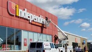 Rochdi's name goes up on the uptown Independent grocery store on July 8. Michele Taylor/Cabin Radio