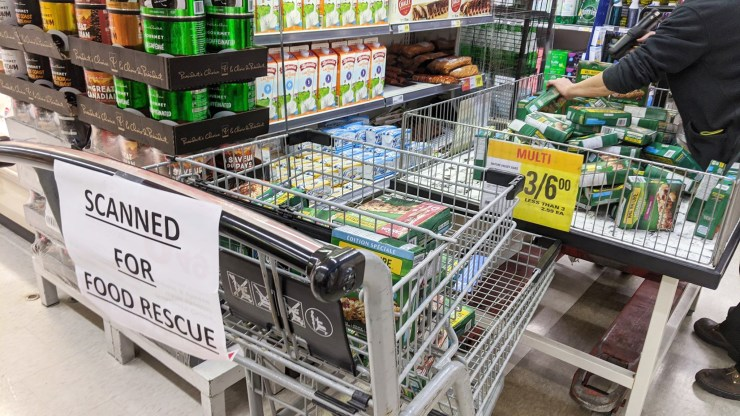 An employee scans food damaged by water in a sprinkler malfunction for Food Rescue Yellowknife. Sarah Pruys/Cabin Radio