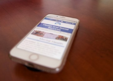 A cellphone shows the website of the Department of Health and Social Services