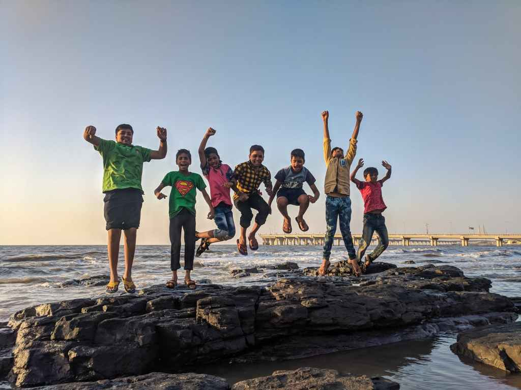 boy wearing green crew neck shirt jumping from black stone on seashore