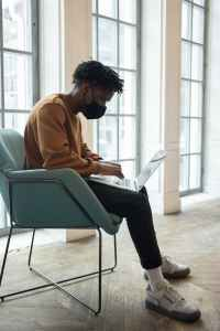 black employee in fabric mask working on laptop in armchair