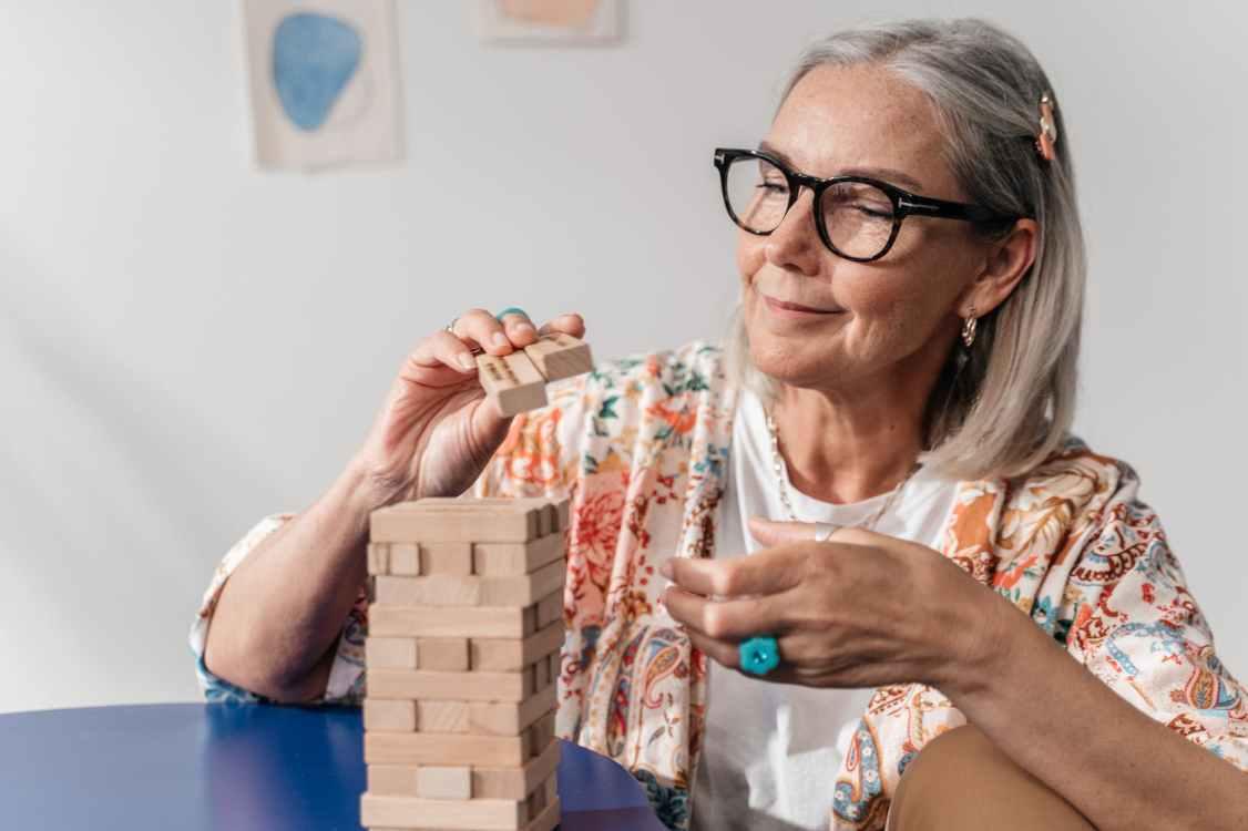 close up shot of an elderly woman with eyeglasses playing jenga blocks