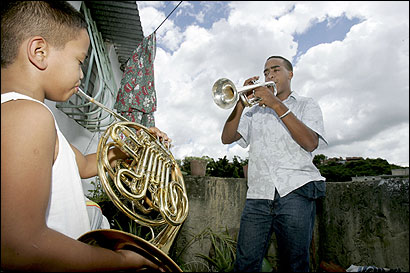 Wilfrido Galarraga, 21, played trumpet on the roof of his home in La Vega, a poor neighborhood on the outskirts of Caracas, as his nephew Onil Galarraga, 8, joined in on French horn.