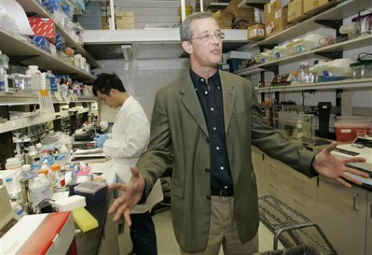 Dr. John Kelsoe, co-founder of Psynomics, explains his research in a laboratory at the University of California-San Diego as faculty member Dr. Xianjin Zhou works behind, Thursday, Feb. 28, 2008 in San Diego. Kelsoe has spent his career trying to identify the biological roots of bipolar disorder.