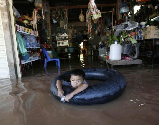 A boy played in flood waters yesterday at a shop east of Vientiane, the capital of Laos. Officials there said the flooding of the Mekong River was the worst in memory.