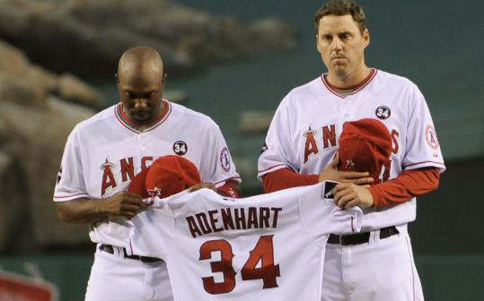 Torii Hunter and John Lackey hold the jersey of Nick Adenhart in pre-game ceremonies honoring Adenhart. They are also wearing the No.34 patch in memory of Adenhart.