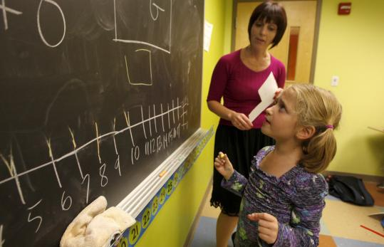 Student Michelle Finkielsztein works on a problem in Irena Burmistrovich's kindergarten class at the Russian School of Mathematics in Newton.
