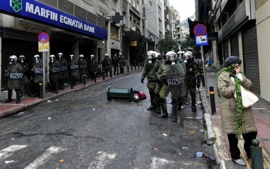 Riot police guarded a bank in Athens yesterday during a nationwide protest against the government?s latest austerity measures.