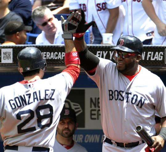 David Ortiz greets Adrian Gonzalez after Gonzalez's two-out home run in the first inning.