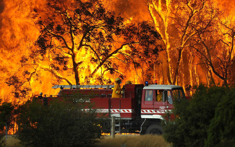 A fire truck moves away from out of control flames from a bushfire in the Bunyip Sate Forest near the township of Tonimbuk, 125 kilometers (78 miles) west of Melbourne, Saturday, Feb. 7, 2009. Walls of flame roared across southeastern Australia, razing scores of homes, forests and farmland in the sunburned countrys worst wildfire disaster in a quarter century. (AP Photo)