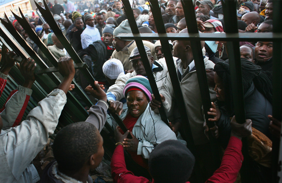 Immigrants, most from Zimbabwe, rush the gate to apply for refugee asylum permits at a government refugee center June 17, 2008 in Johannesburg, South Africa. Officials were overwhelmed by the crowd of thousands that appeared Tuesday morning, after a three day weekend in South Africa. The wave of immigrants crossing illegally from Zimbabwe continues, despite the xenophobic violence against immigrants last month. (Photo by John Moore/Getty Images)