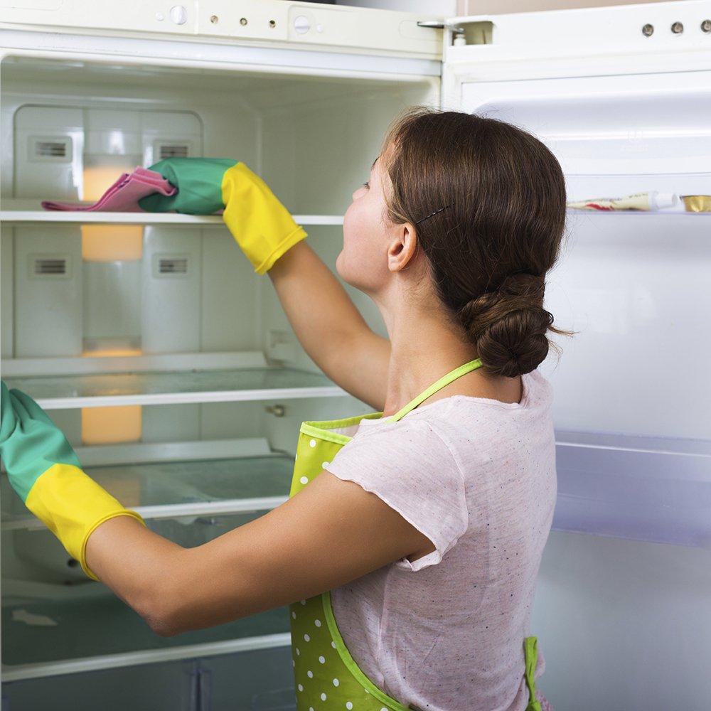 femme qui nettoie l interieur de son frigo avec des gants jaunes et verts