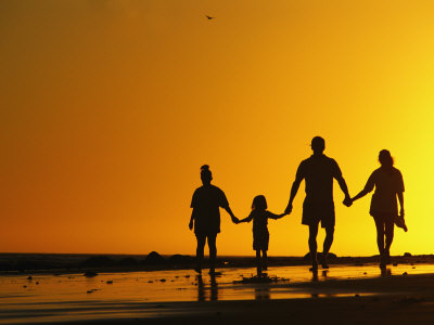 A Family Holding Hands is Silhouetted against the Setting Sun Photographic Print