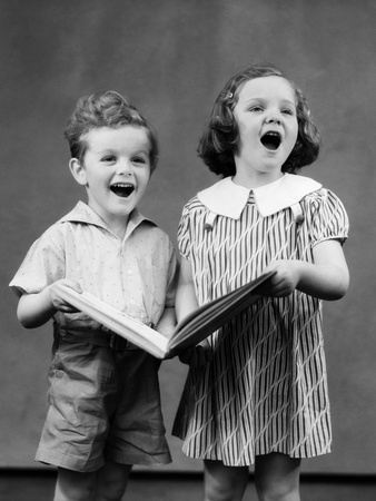 Black and white photograph, boy and girl about four years old together holding a large book and singing