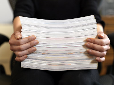 A woman holding a large stack of paper.