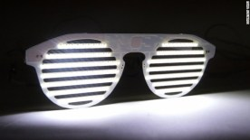 """Los lentes estilo persiana, popularizados por el rapero y seguidor de moda, Kanye West, están en plena transformación: de ser un efímero accesorio, se volverán una ingeniosa herramienta para el aprendizaje tecnológico. Sus fabricantes esperan que gracias a ellos, más personas se animen a aprender el arte de la programación de computadoras. El Bright Eyes Kit contiene un par de lentes fabricados completamente con placas para circuitos y está salpicado con 174 luces LED adheridas al frente. """"Puedes controlar cada LED individualmente"""", explica Daniel Hirschmann, uno de los fundadores de Technology Will Save Us (TWSU), la nueva empresa londinense detrás de la idea. La pequeña matriz puede mostrar texto en desplazamiento, videos de llamas parpadeantes o generar cualquier imagen en movimiento que el usuario desee. """"Bright Eyes es nuestra misión para convencer a la gente de que aprendan a programar"""", dice Hirschmann, quien espera que conforme los dispositivos cotidianos desarrollen la capacidad de enviar y recibir datos –una tendencia que a veces es llamada """"el internet de las cosas""""— será más importante que sepamos cómo manejarlos y adaptarlos. TSWU está siguiendo los pasos de la Raspberry Pi, la computadora de 25 dólares diseñada para alentar a los niños a aprender programación. Sin embargo, las centelleantes luces del Bright Eyes Kit son un incentivo adicional: aprendes a programar y luces cool en el proceso. """"Sin el incentivo, no tenemos un argumento convincente, así que pensamos en crear (uno)"""", dice Hirschmann. Lo más importante es que los usuarios pueden elegir qué tanto quieren profundizar en el programa, que va desde una interfaz básica de """"arrastrar y soltar"""" hasta la programación completa, línea por línea. Conforme la tecnología penetra inexorablemente en cada rincón de nuestras vidas, algunos consideran que tener un entendimiento rudimentario de la programación computacional es indispensable. Para Zach Zimms, uno de los fundadores de Code Academy (un recurso in"""