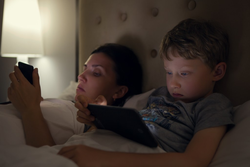 Mother with son looks in their electronic devices lying in bed