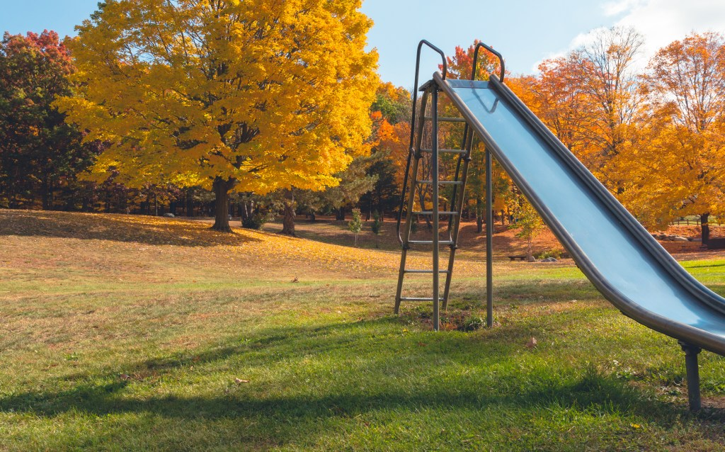 A colorful playground in the fall with a metal slide in the foreground.