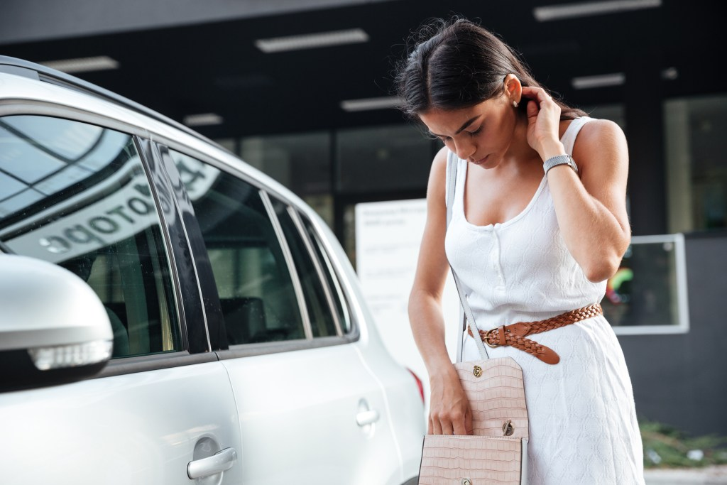 Woman standing looking keys of car in bag