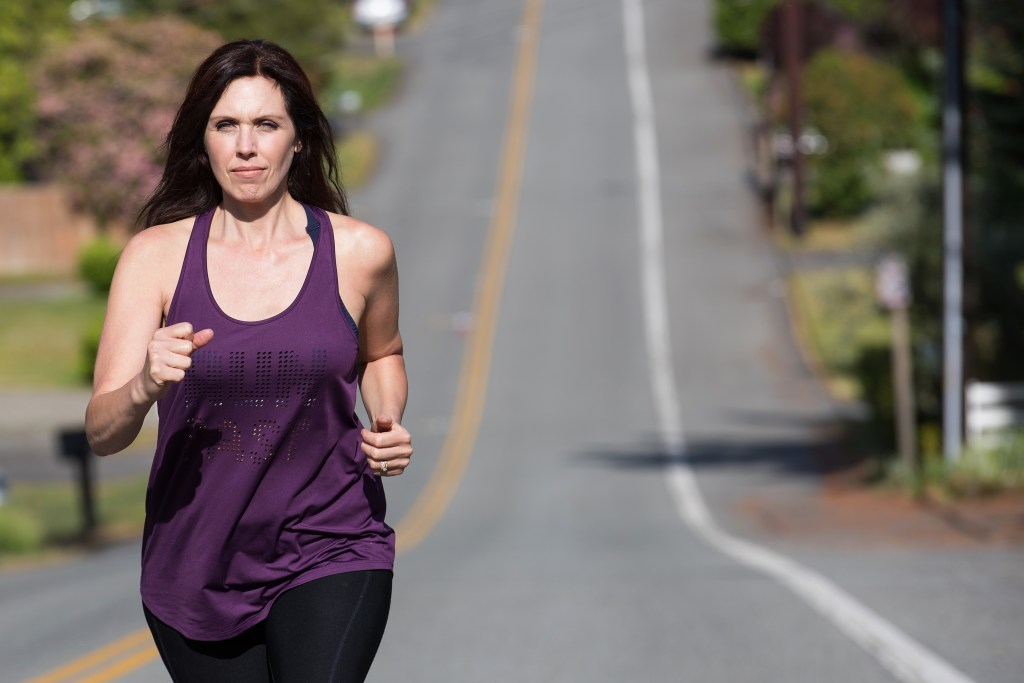 Healthy woman running uphill