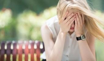 Sad woman sitting on bench outdoors