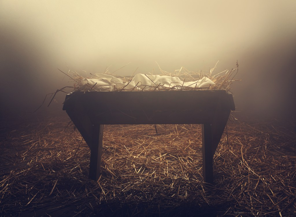 An empty manger at night under the fog.