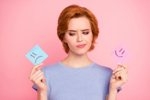 Woman looking at happy or sad post it notes