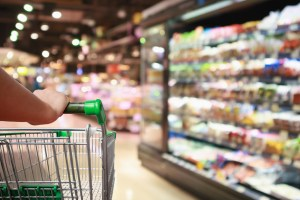 woman hand hold supermarket shopping cart with Abstract grocery store
