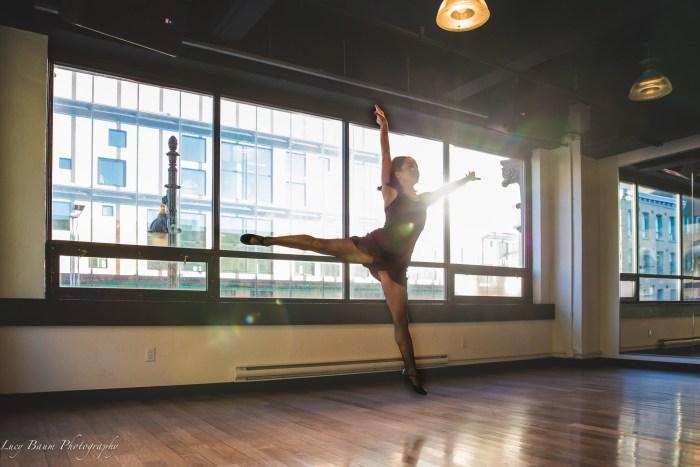 jazz dancer jumping in an arabesque position