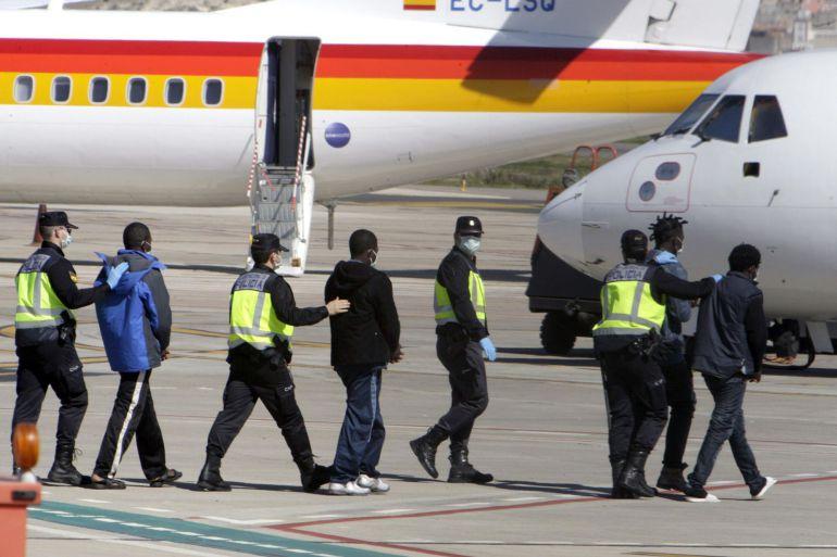 Agentes de la Policía Nacional trasladan hasta el avión a un grupo de inmigrantes desde Melilla un CETI de la Península