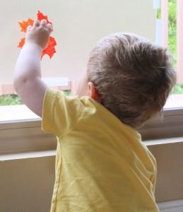 Falling leaves child reaching thru pane