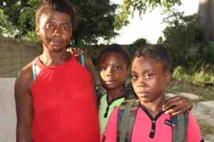 Jeunes du CAEJ-Haïti avec leur maman et leurs effets scolaires