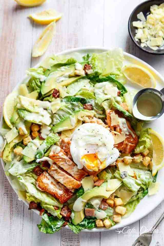 Crispy pan fried Salmon meets Caesar salad for a twist on the traditional! Easy to make with creamy avocado slices, crunchy croutons, the tang of shaved parmesan cheese, a perfect runny poached egg on top and a lightened up Caesar dressing!| http://cafedleites.com