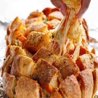 This Garlic Butter Pizza Pull Apart Bread is smothered in garlic butter, stuffed with pizza fillings, and topped with so.much.cheese! | http://cafedelites.com