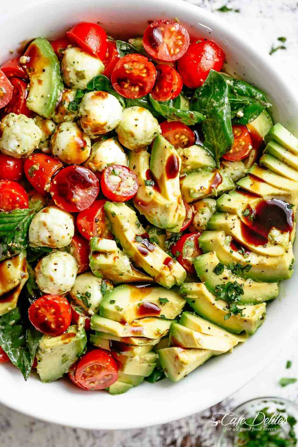 Caprese salad with creamy avocado slices and a delicious basil pesto dressing! | cafedelites.com