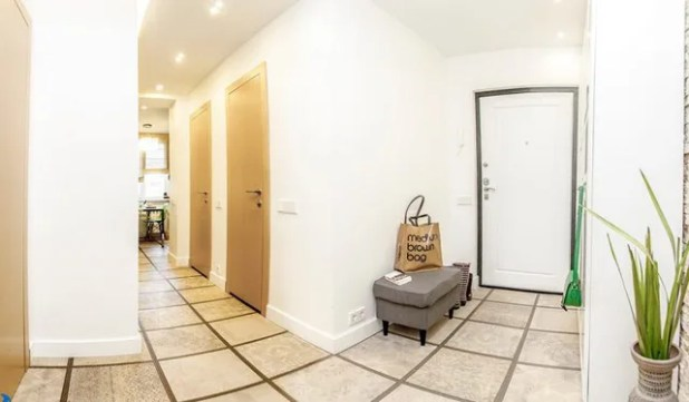 Lối vào nhà được bài trí khá đơn giản, thoáng sáng với gam màu trắng chủ đạo.