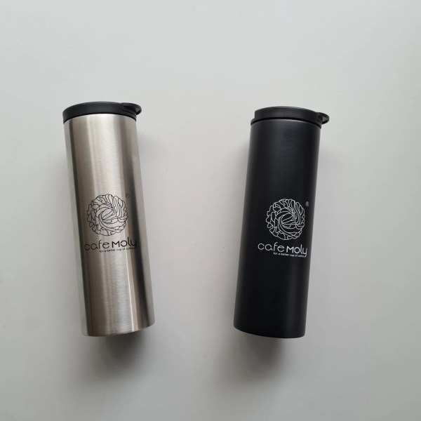 Display of two Cafe Moly Thermos. Black and silver thermos lying side-by-side.