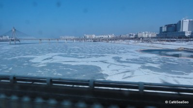 The mostly frozen Han River seen from the metro