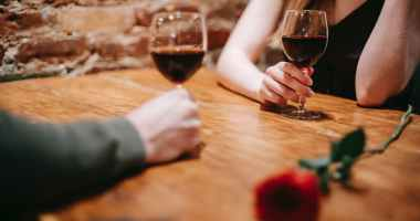 unrecognizable couple in restaurant on date with wineglasses