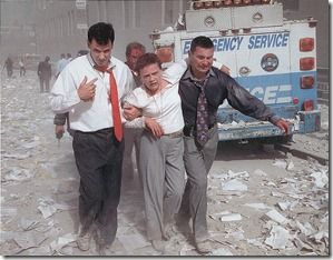 [Two men assisting and walking with an injured woman down a street littered with paper and ashes, following the September 11th terrorist attack on the World Trade Center, New York City] / Don Halasy