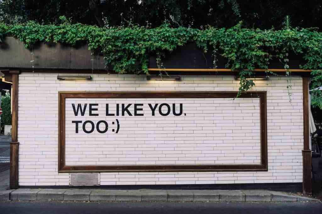 "A photograph of a white brick wall with text overlay ""we like you, too :)"""