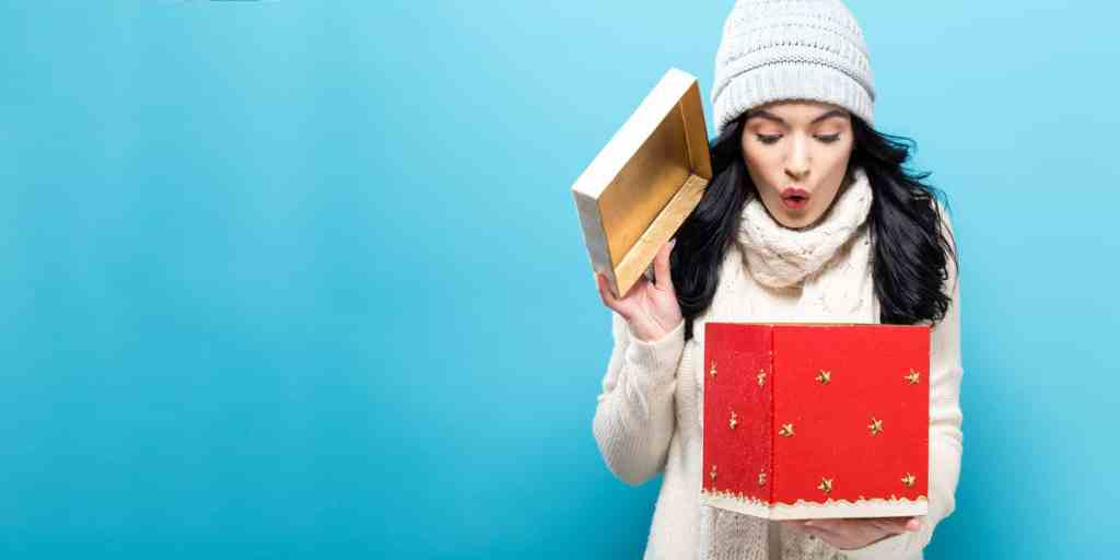 Happy young woman opening a Christmas present box.