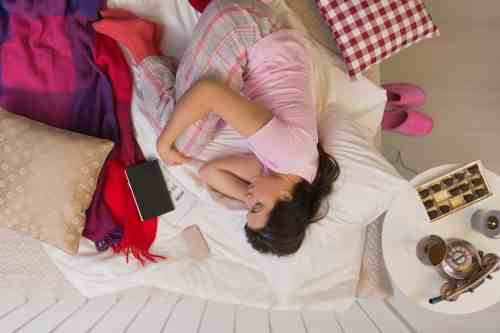 Woman having winter depression, lying in bed