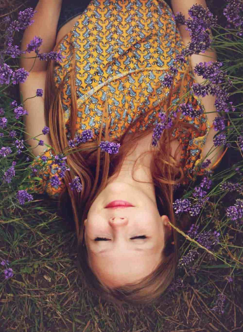 A young woman laying in the grass with purple flowers
