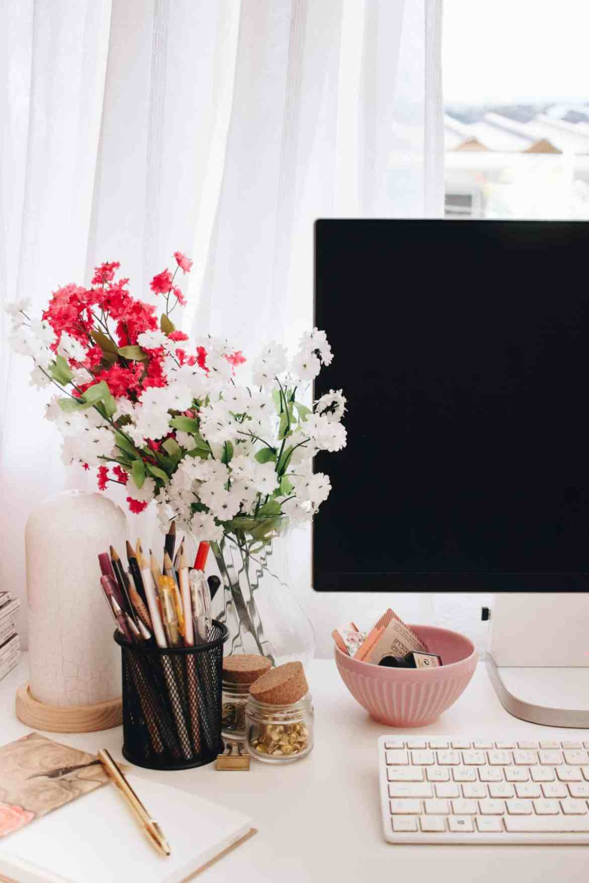 A computer screen on a desk in front of a window with flowers and other objects on the desk