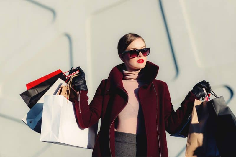A fashionable woman wearing sunshades and holding half a dozen shopping bags