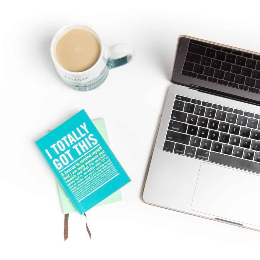 A laptop, book and cup of coffee